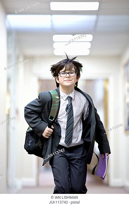 Portrait smiling middle school student running in school corridor