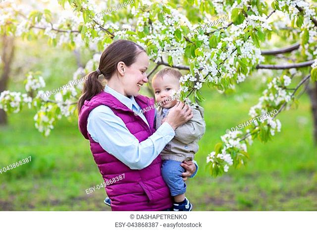 Little baby boy with his young mother in the blossoming spring garden