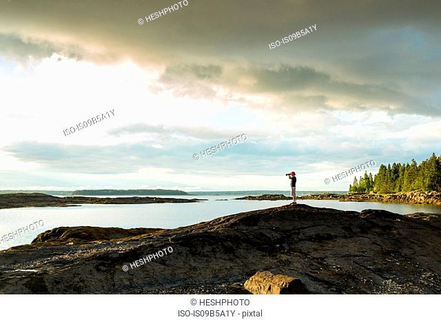 Distant view of senior man looking through binoculars at coast of Maine, USA
