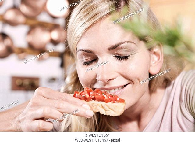 Italy, Tuscany, Magliano, Young woman smelling tomatoes on bruschetta, smiling