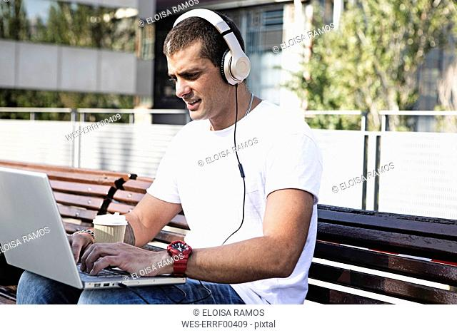 Young man sitting on a bench wearing headphones and using laptop