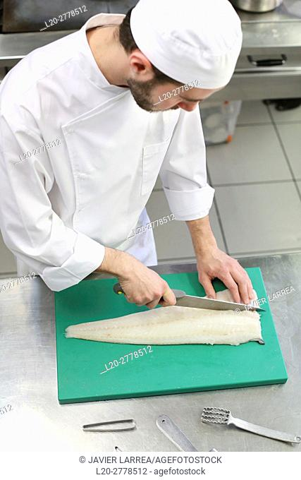 Chef cutting cod, Cook in cooking school, Cuisine School, Donostia, San Sebastian, Gipuzkoa, Basque Country, Spain, Europe