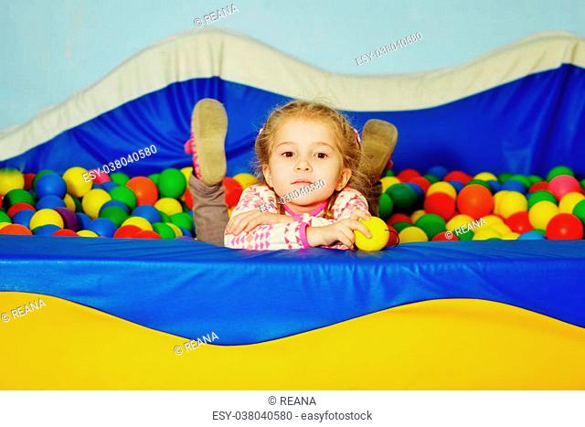 little girl playing in playground colourful ball pool