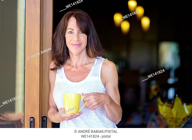 A mature woman is smiling at the camera while leaning at a door frame and holding a coffee mug