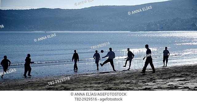 Boys playing football on the beach in Tangier, Morocco, Africa