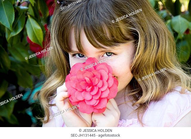 Picture of girl (8-9) smelling flower