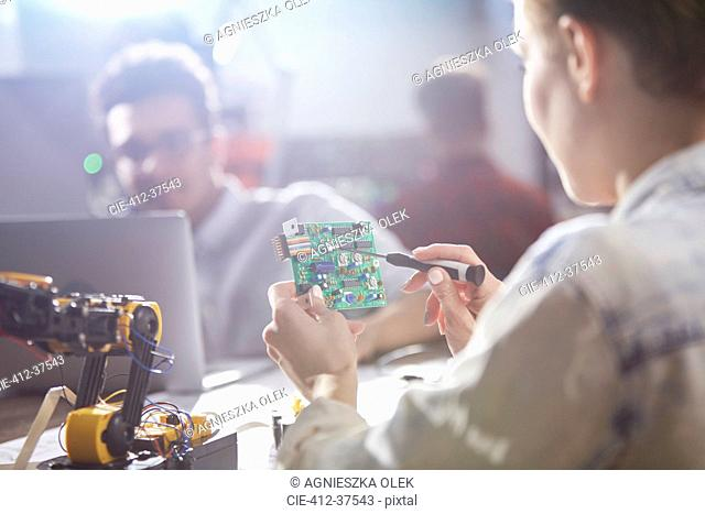 Female engineer assembling circuit board with soldering iron