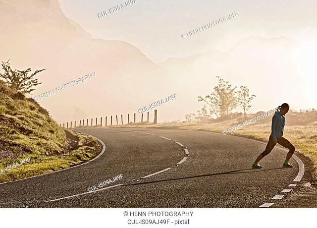 Female runner warming up on roadside, Capel Curig, Snowdonia, North Wales, UK