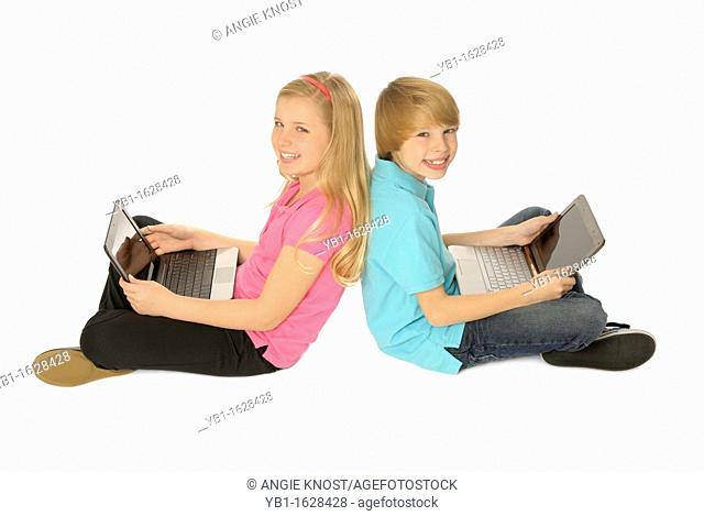 Two siblings using laptop computers, sitting back to back  Boy is eleven years old, girl is ten years old