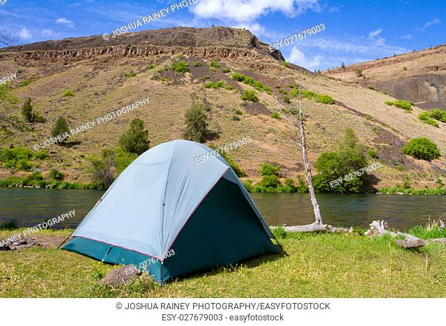 A rustic tent campsite on the Deschutes River in Oregon shows a tent setup next to a boat and the river. This is form a float camping trip