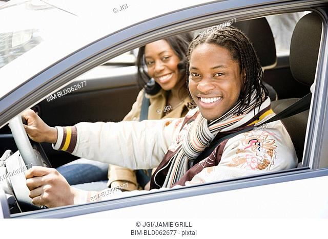 African couple driving in car