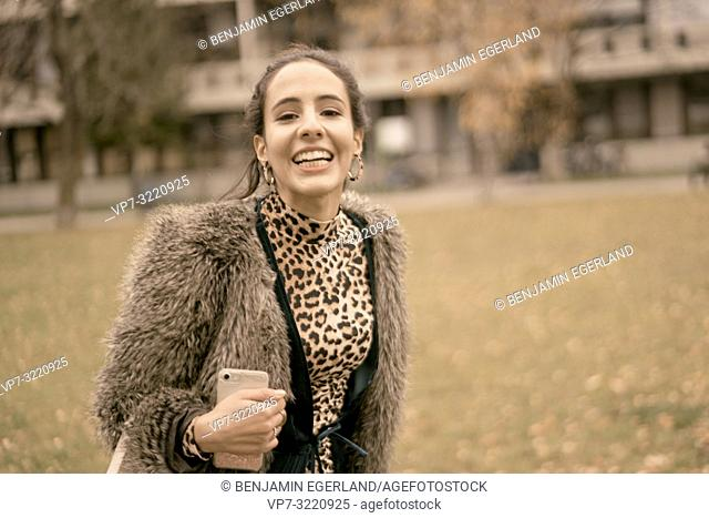 fashionable lively woman walking outdoors in park, autumn season, wearing coat, happiness, candid emotion, unposed walking in city, Munich, Germany