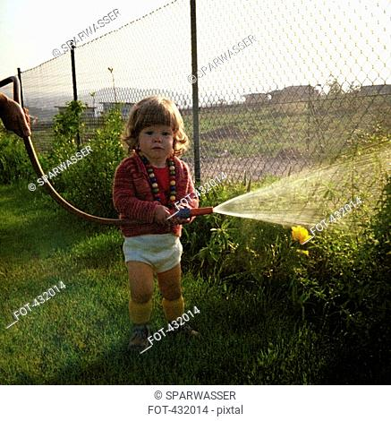 Young girl watering the garden witha hosepipe