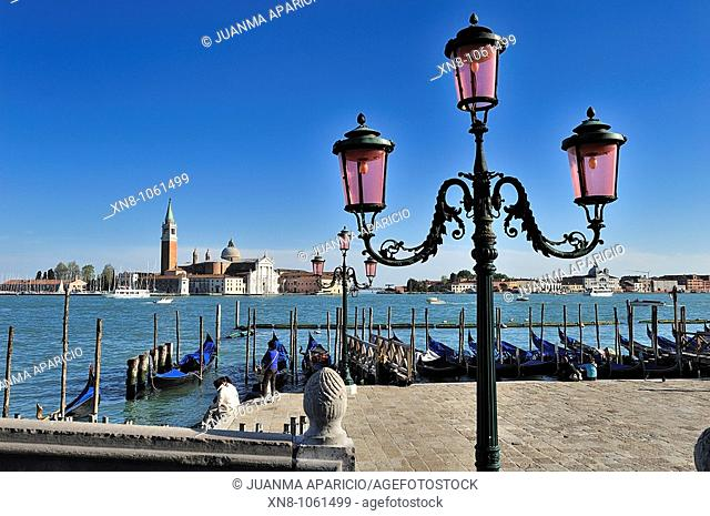 Beautiful wrought iron lamppost photographed from the Palazzo Ducale (Venice, Veneto, Italy) with the landing of gondolas and San Giorgio island in the...