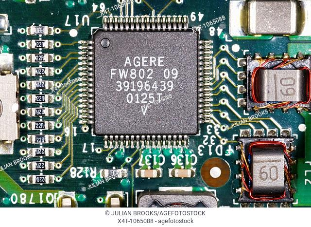close up photograph of electronic components on a computer mother board showing surface mount resistors and an integrated circuit