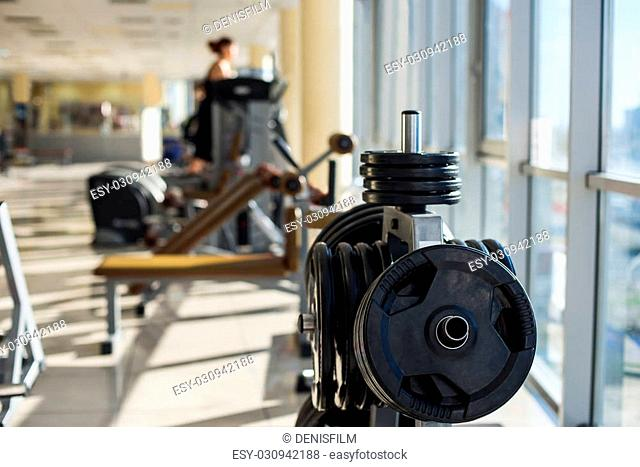 Training apparatus in gym hall. Weight plates hanging on metal rack in gym hall. People are training on background in gym