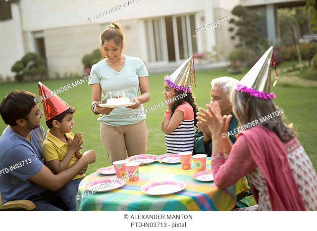 Mother showing birthday cake to young boy (4-5) at party