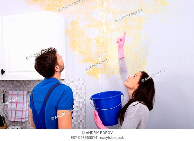 Young Woman With Blue Bucket Showing Water Leaking From Damage Ceiling To Serviceman