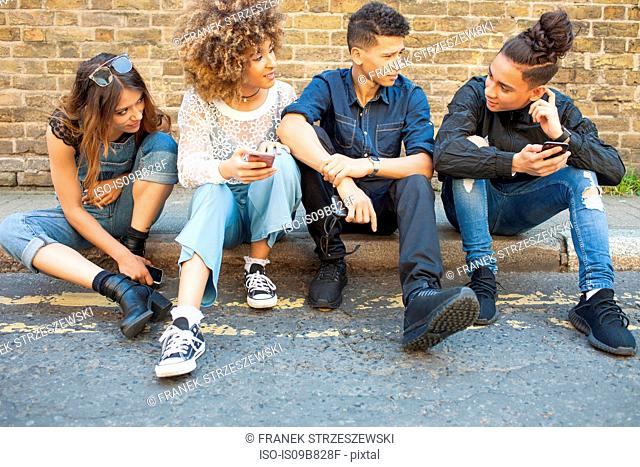 Four friends sitting in street, looking at smartphones