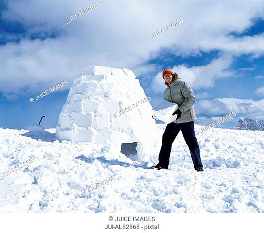 Man holding ice block and building igloo