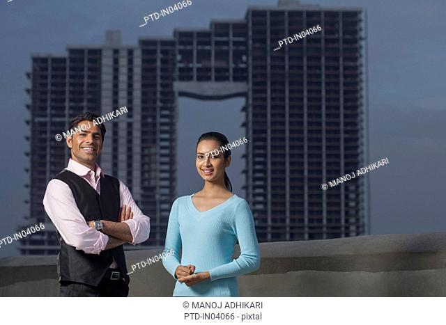 India, Man with arms folded standing next to woman with building under construction in background