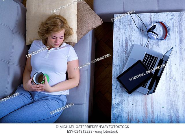 A young plus size woman falling asleep at night on the sofa with a Tablet PC and a Laptop on the Table.