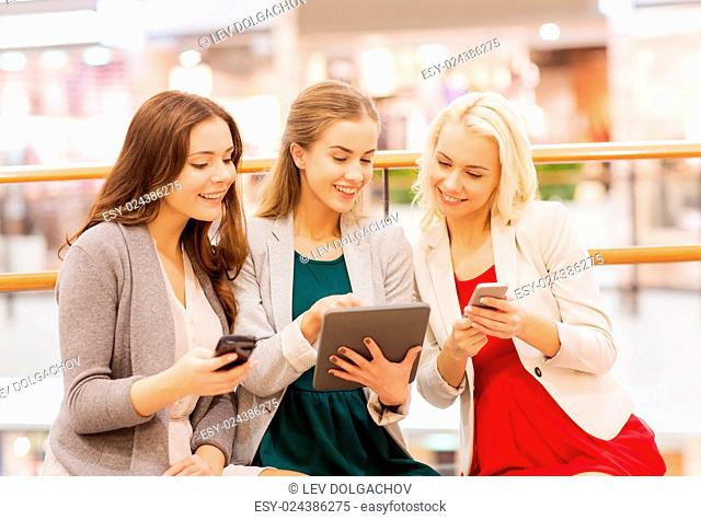 sale, consumerism, technology and people concept - happy young women with smartphones and tablet pc in mall