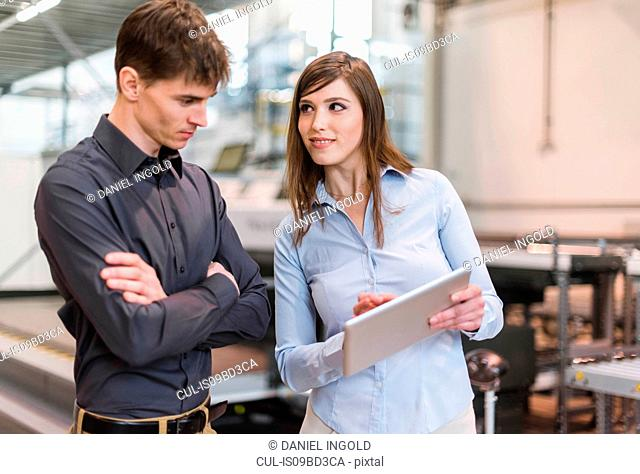 Two colleagues in industrial building, having discussion, looking at digital tablet