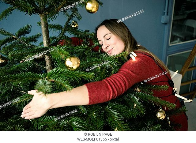 Woman hugging Christmas tree