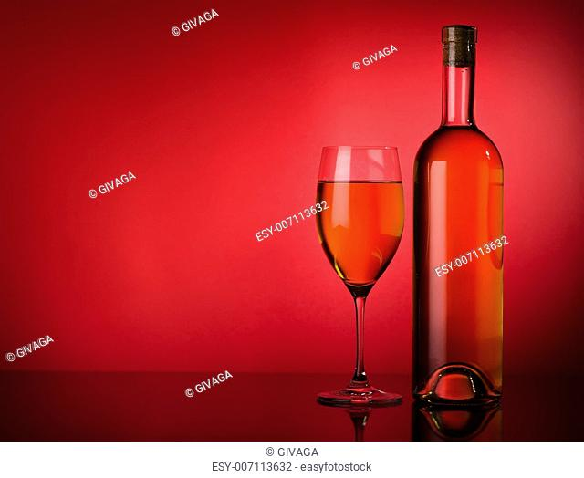 Buttle and glass of white wine on a red background