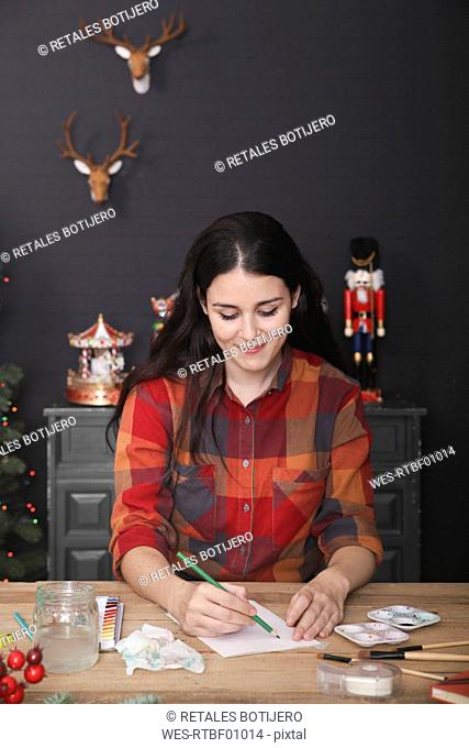 Smiling young woman drawing Christmas card
