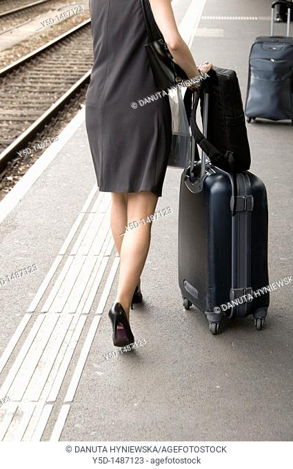 travelling woman with suitcase and bags, high heel, dress, main train station, Geneva, Switzerland