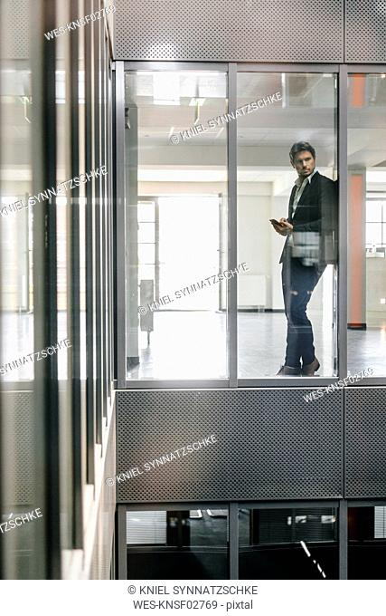 Businessman standing at window, holding smartphone