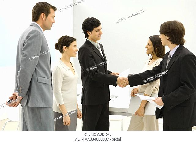 Business associates meeting, shaking hands while others watch