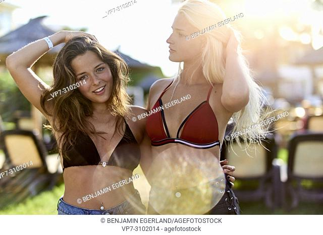Sensual, playful women in bikini at holiday resort, enjoying summer breeze