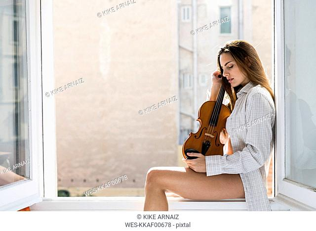 Young woman with eyes closed sitting on window sill holding violin