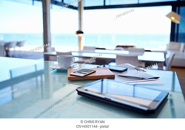 Digital tablet, calculator and coffee on kitchen counter