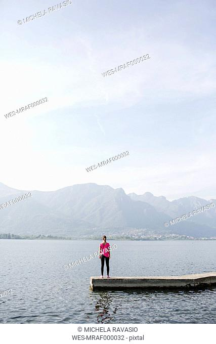 Italy, Lecco, young woman standing at the lake