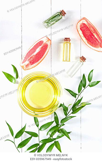 Essential oil in glass bottle with fresh, juicy grapefruit and green leaves-beauty treatment. Spa concept. Top view