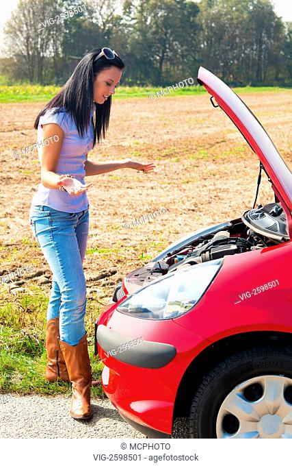 Young woman with her car breakdown. Engine failure - 01/01/2011