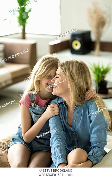 Happy mother and daughter cuddling and relaxing on a couch in a modern living room