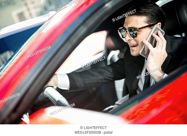 Businessman in car on cell phone