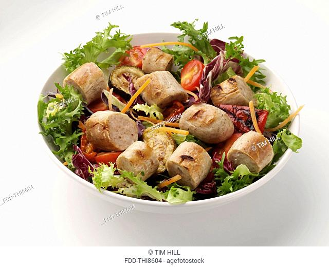 A bowl of bratwurst with salad on a neutral background