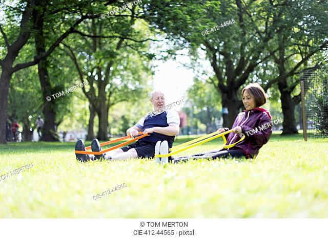 Active senior couple exercising, using resistance bands in park