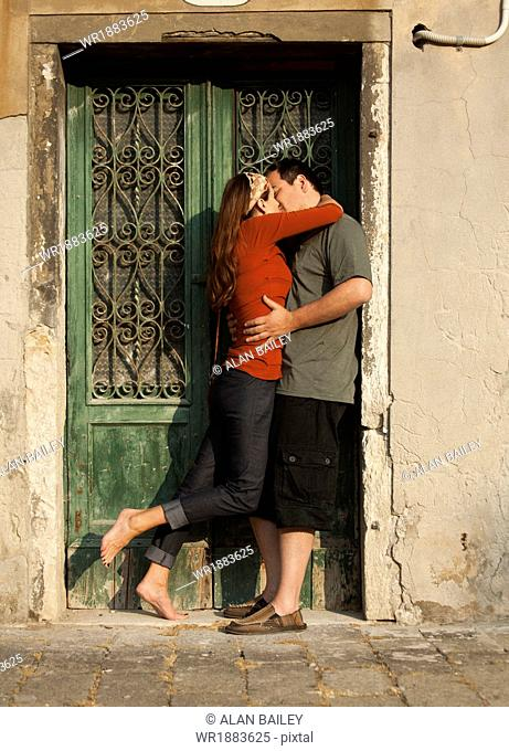 Italy, Venice, Couple kissing by wooden door in old town