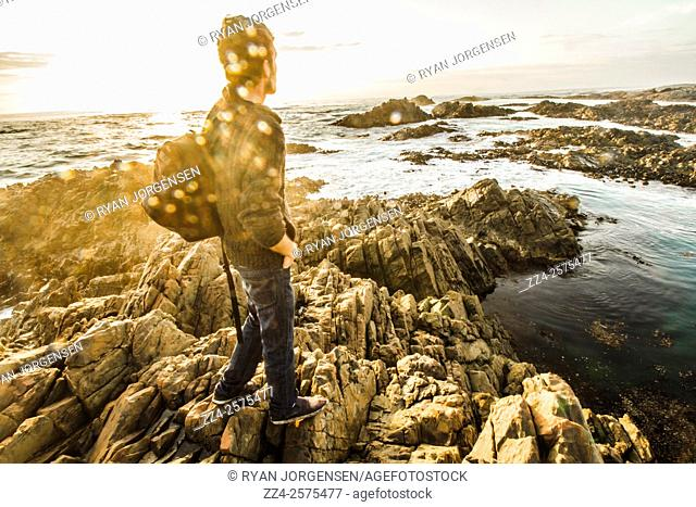 Creative retro picture of a happy young man enjoying the peaceful calm of a tasmanian sea getaway. Real life sun flare capture