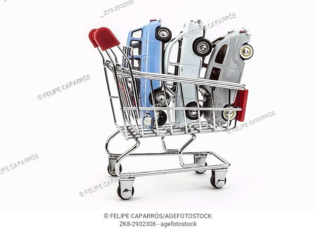 Traditional shopping cart full of miniature cars, business concept