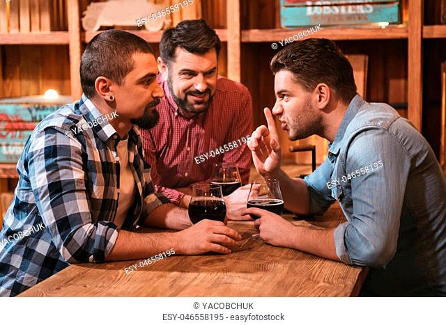 Do not tell anyone. Pleasant nice handsome man sitting with his friends and telling them a secret while drinking beer