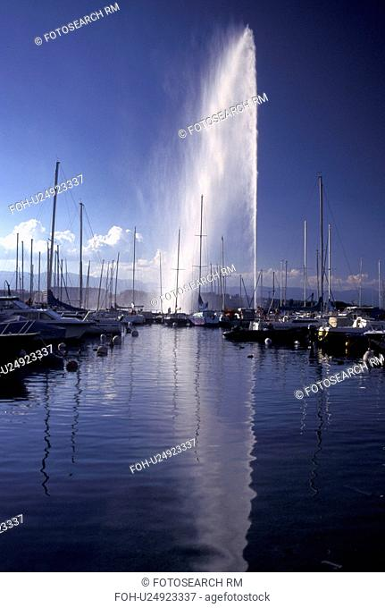 Geneva, Switzerland, Lake Geneva, Jet d' Eau sprays water high above the boats docked at a marina in the harbor of Lac Leman in Geneva