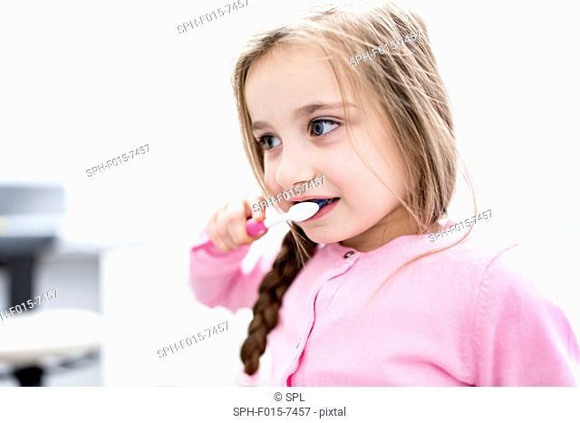 MODEL RELEASED. Girl brushing teeth, close-up